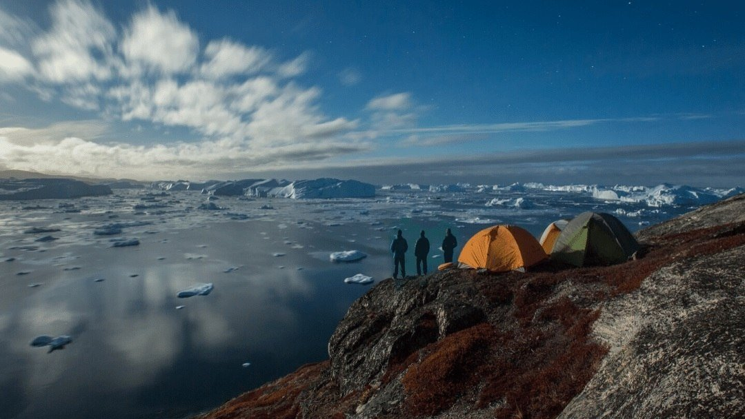 three campers and tents overlooking bay with icebergs in Greenland