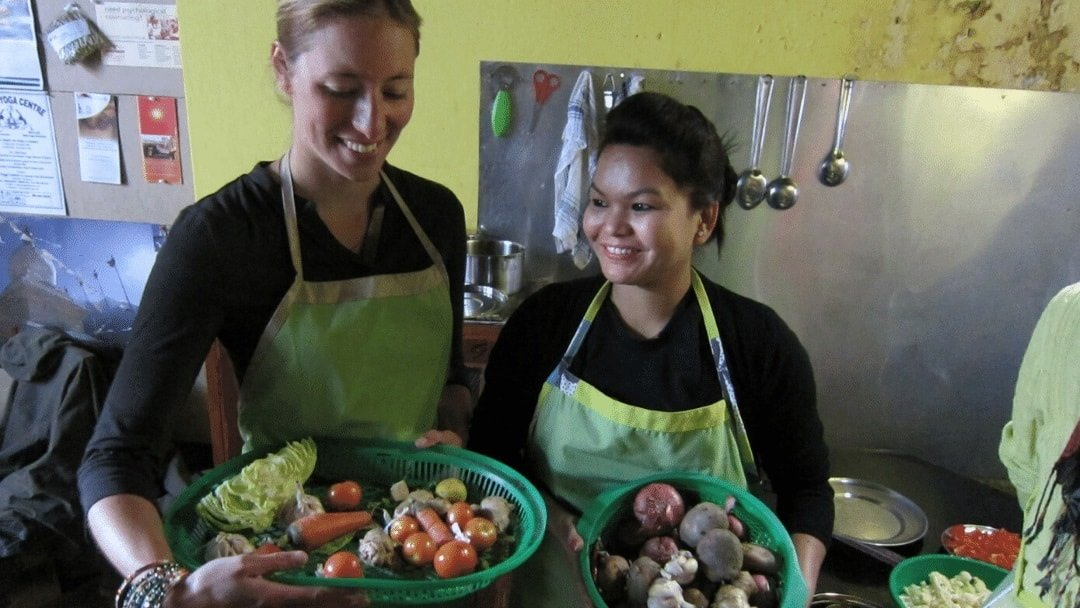 two women in aprons holding baskets in cooking class in Nepal
