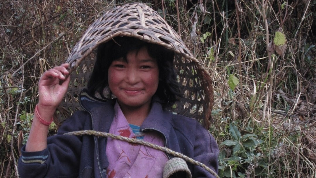 Young Nepal girl with basket on head