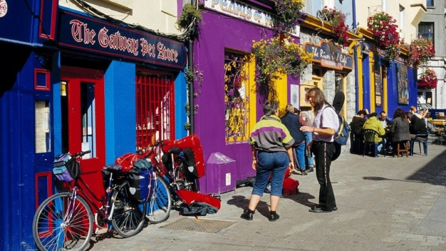 Persons and bicycles outside colorful Irish pub