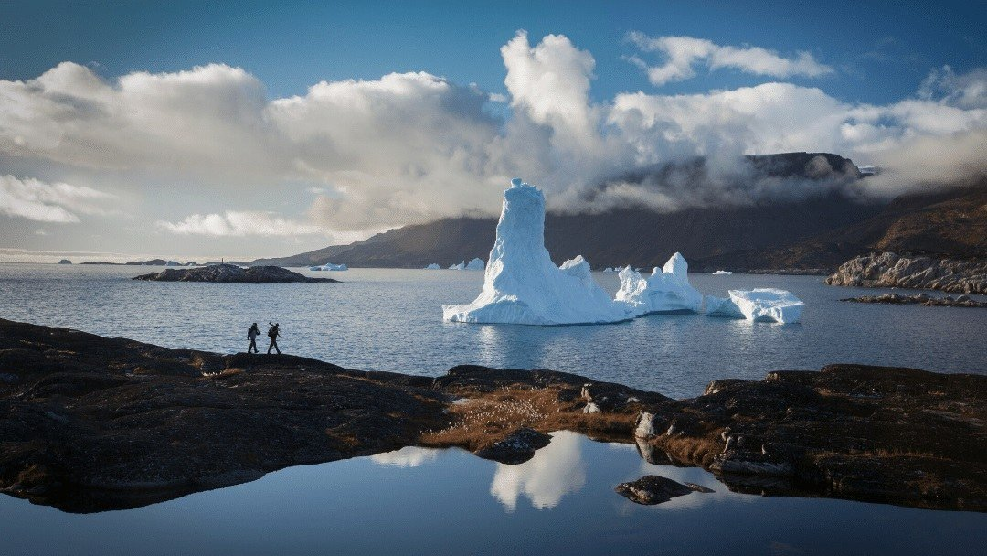 hikers on land with iceberg in water