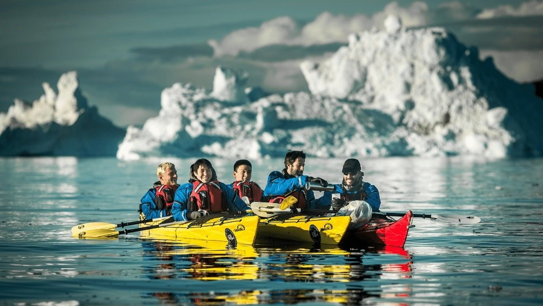 kayakers in Greenand taking coffee break with icebergs in background