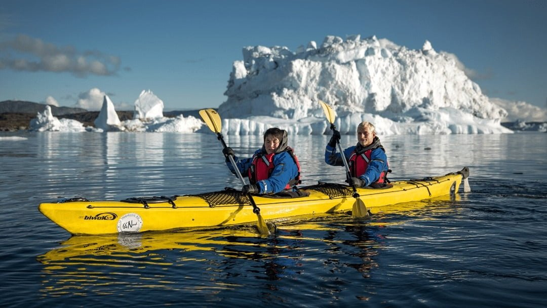 two kayakers and icebergs in Greenland