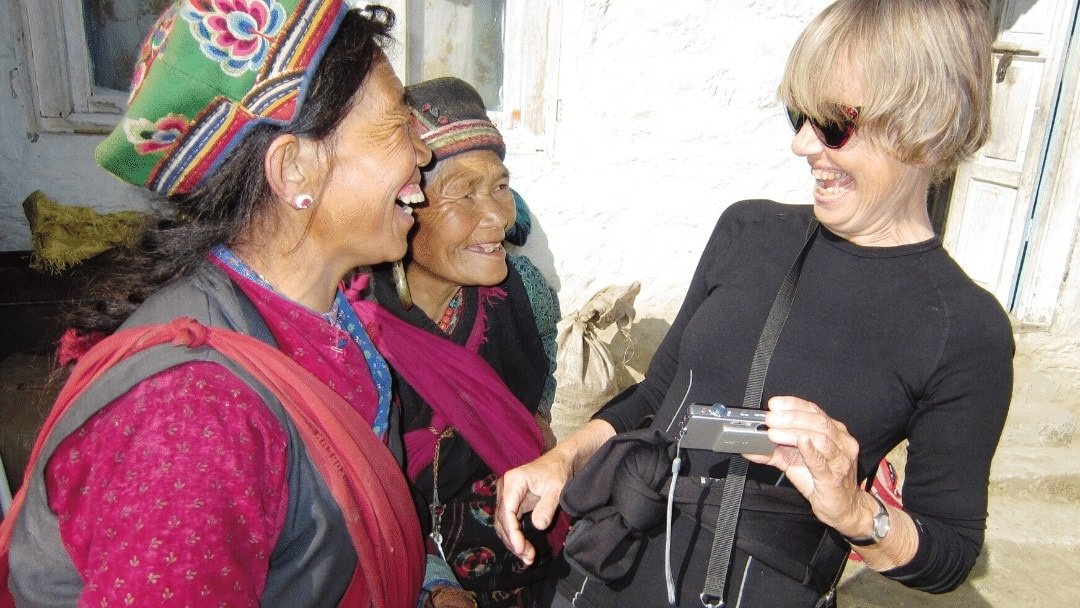 tourist with camera laughing with two Nepalese women