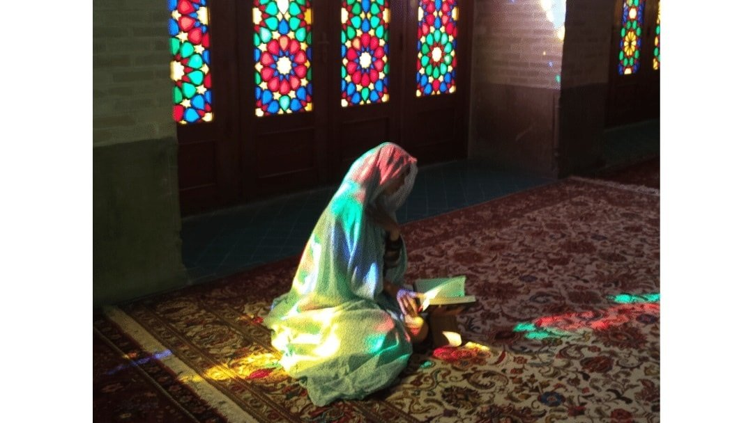 shrouded woman sitting in front of stain glass windows in Iran