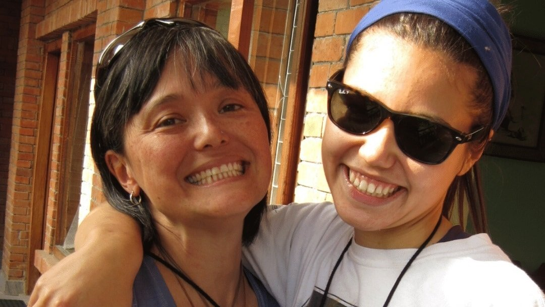two women with big smiles, the younger one wearing sun glasses