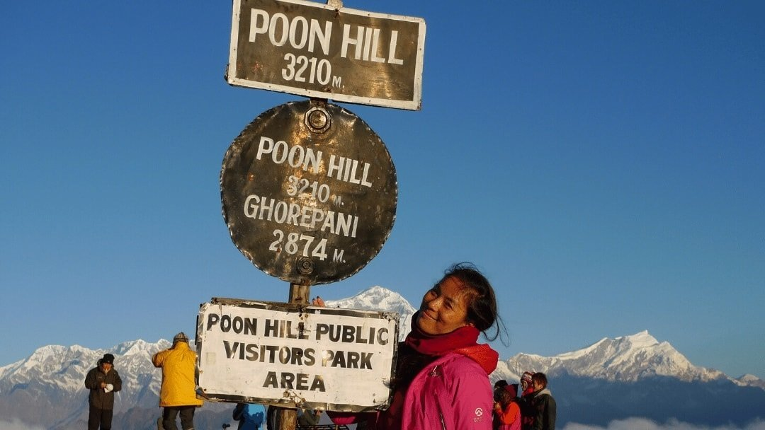 hiker atop Poon Hill Nepal with the Annapurna mountains in background