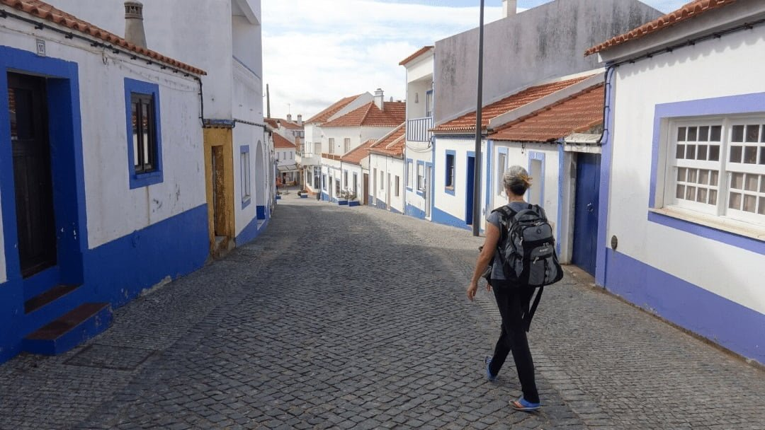 woman walking down deserted cobblestone street filled with blue and white painted houses