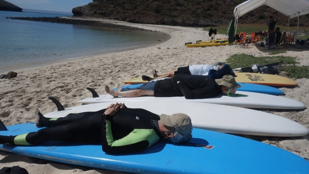 Meaningful Trips guests taking siesta on paddleboards in Baja