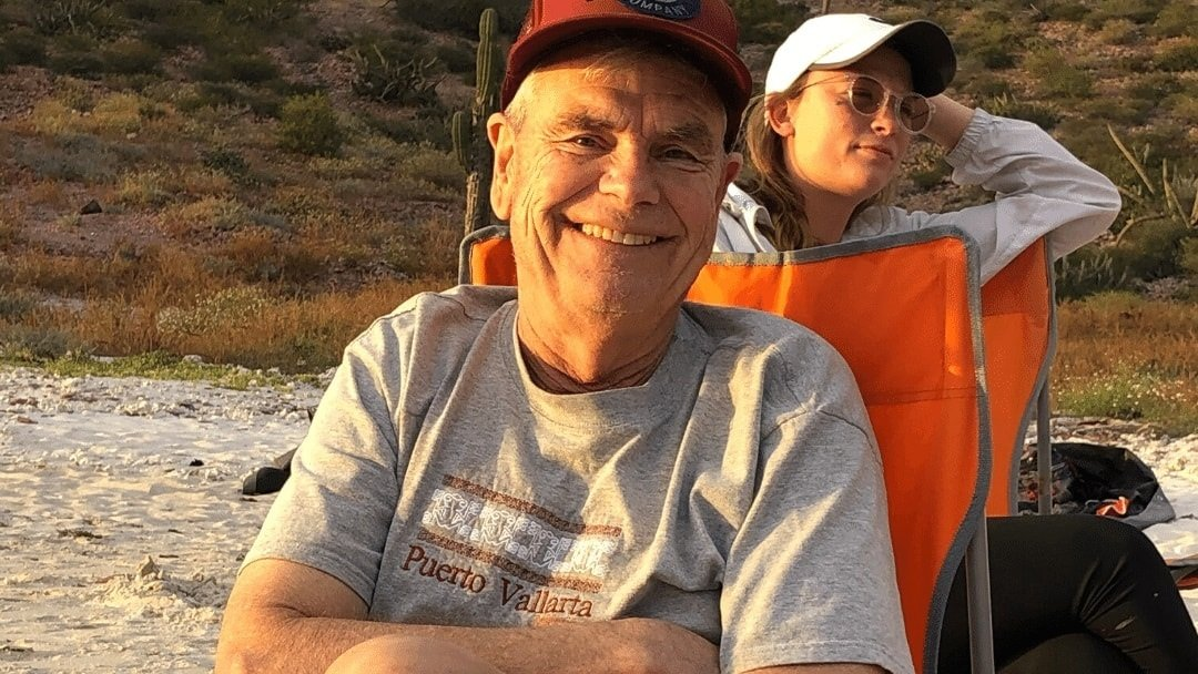 Man smiling while stiing in chair on Baja beach