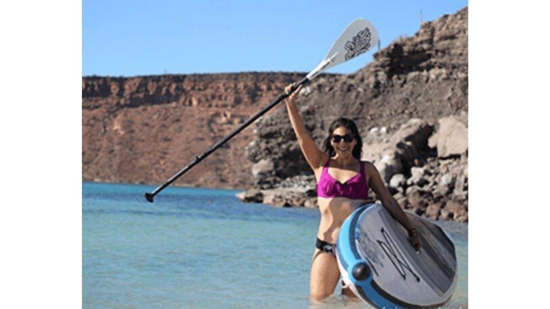woman in bikini holding standup paddleboard