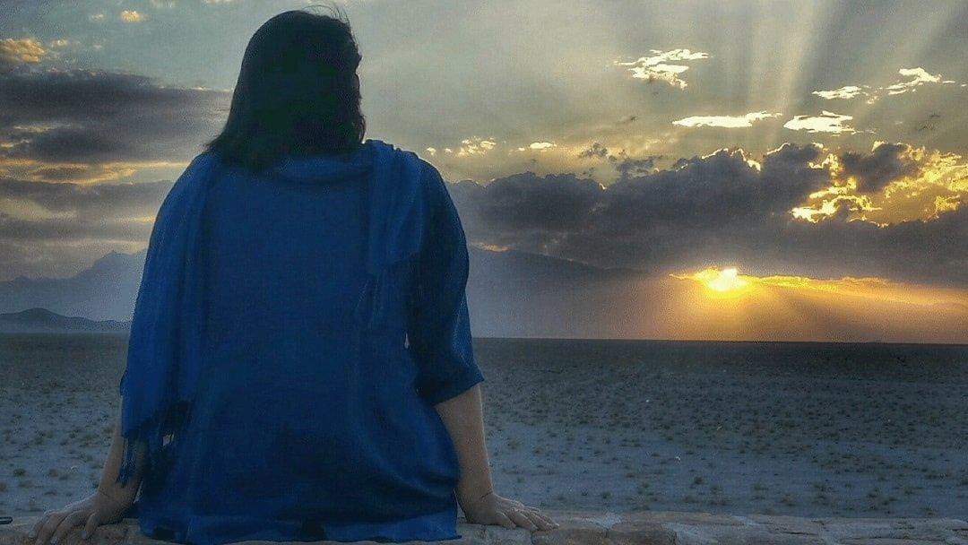woman sitting watching sunset