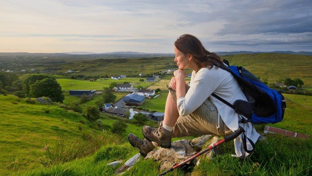 Female hiker resting in green field in Ireland