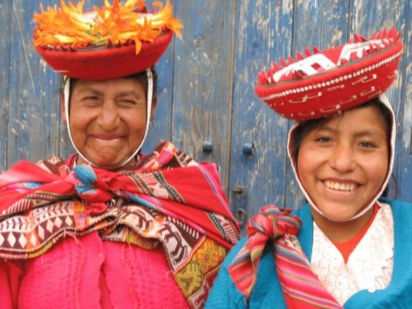 Two smiling south american women wearing traditional clothes and hats