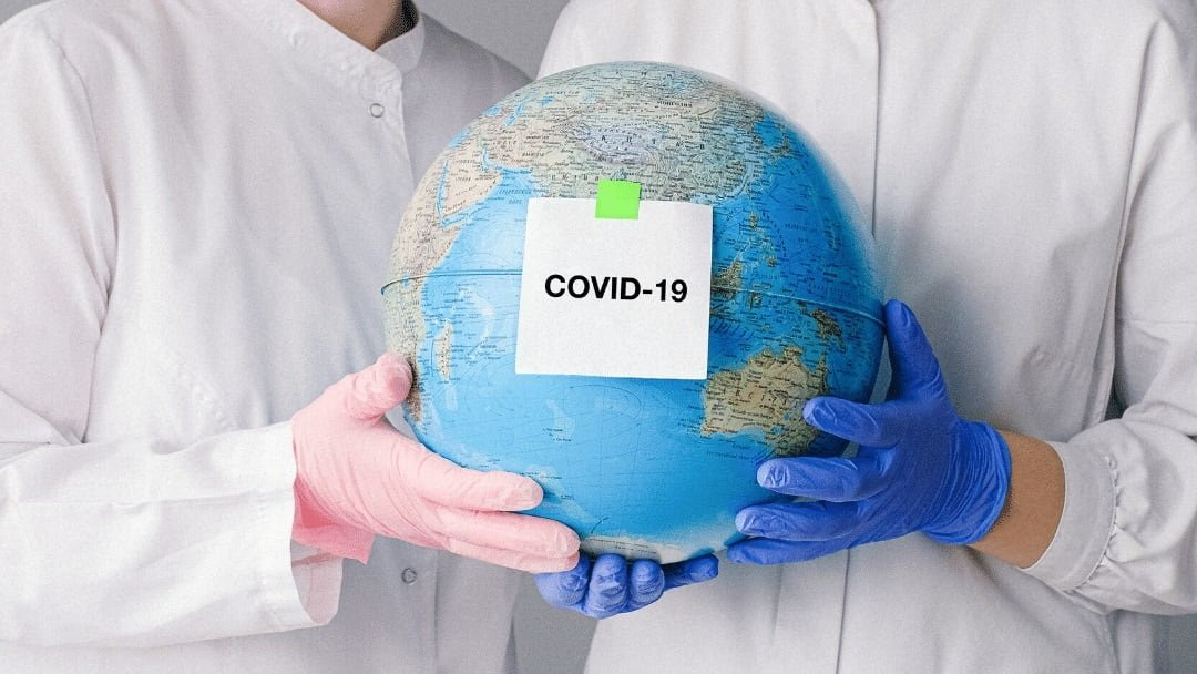two persons in white lab coats and gloves holding globe with note saying COVID-19