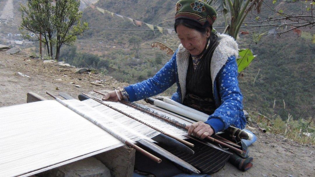 Nepalese woman weaving near trail