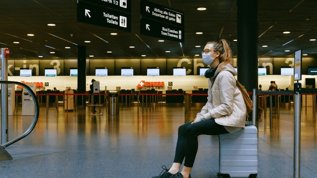 woman with mask on sitting on a suitcase inside an airline terminal