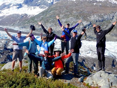 group of 9 hikers posing in Alaska with arms spread