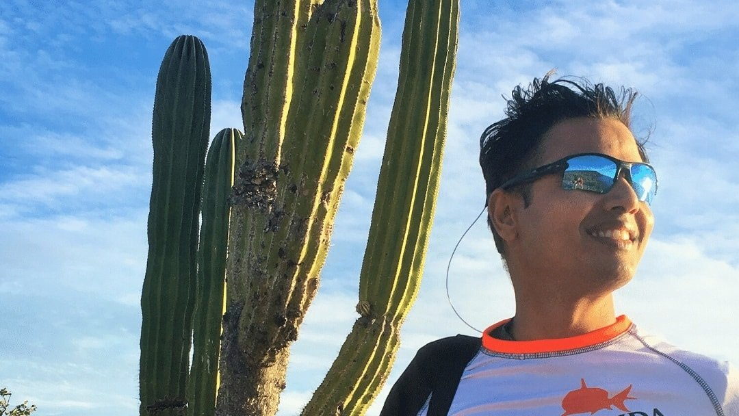 smiling man in front of cactus