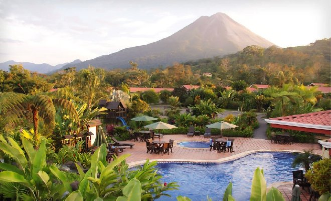Hotel swimming pool with lush trees and volcano in background