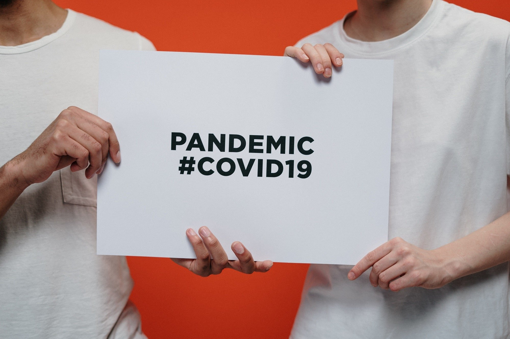 two persons in white t-shirts holding a sign that says pandemic covid19