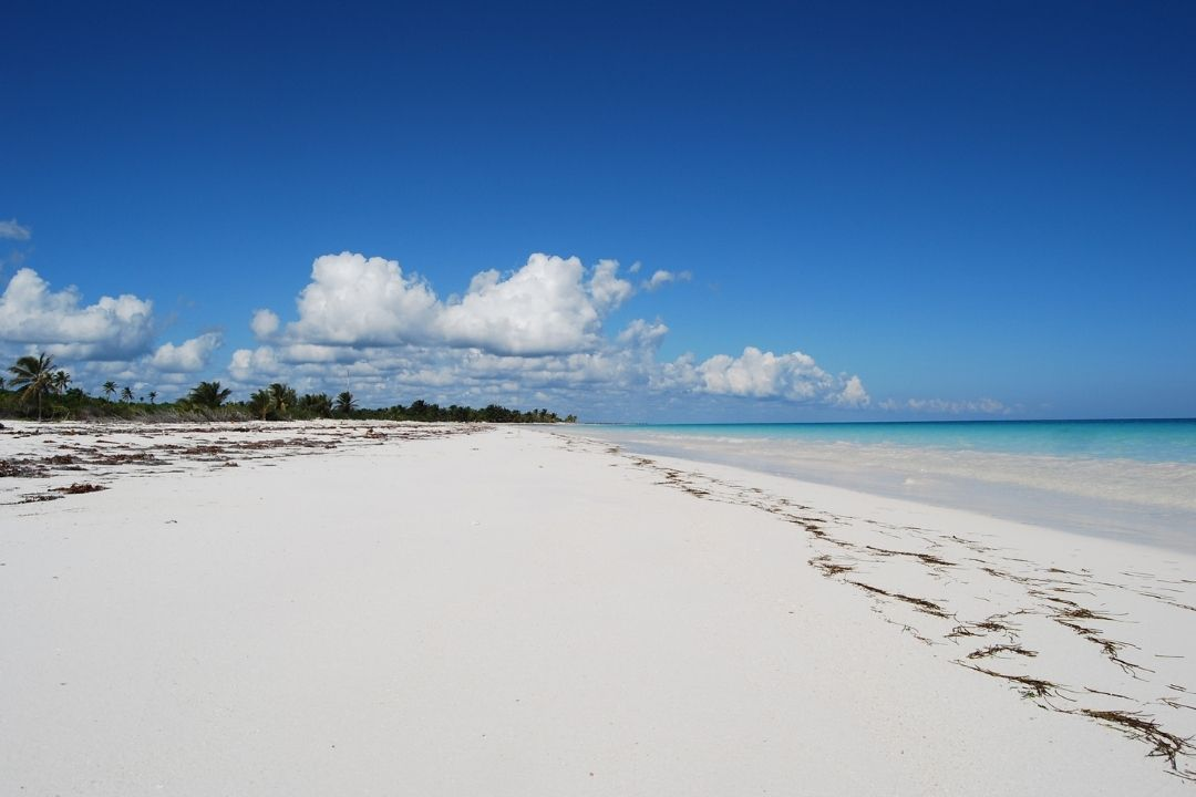 vast, deserted, white sand beach with blue sky and clouds
