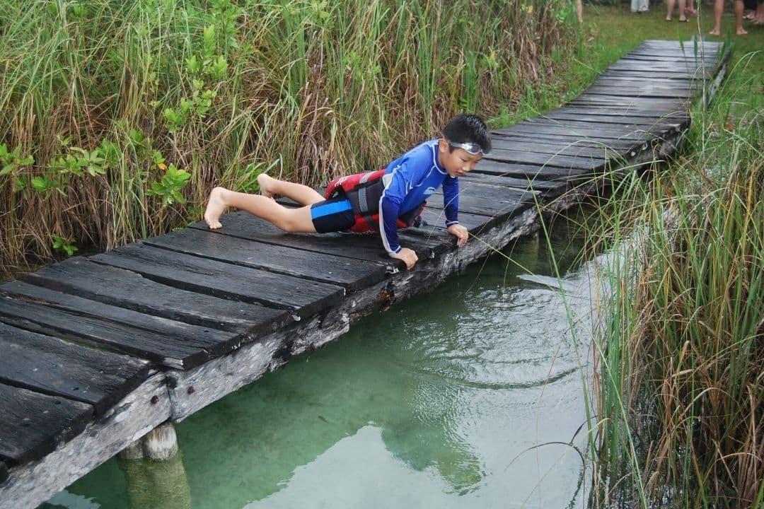 boy lying on a boardwalk over marsh