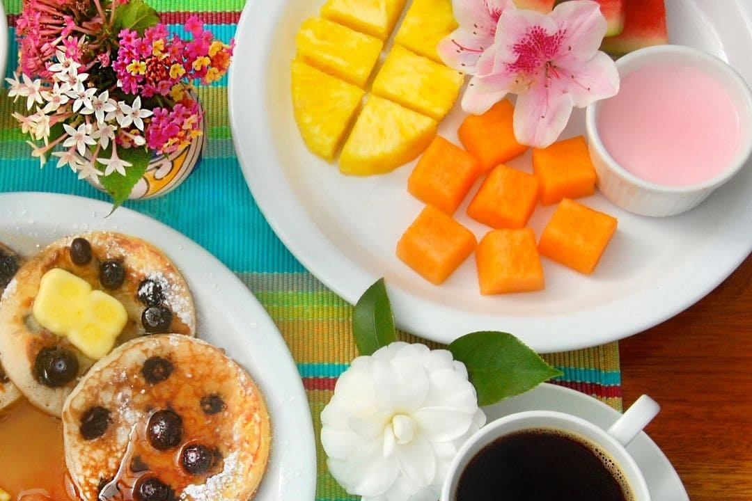 Breakfast setup with one plate of small blueberry pancakes, one plate with pineapple and papaya, coffee mug and small flower vase
