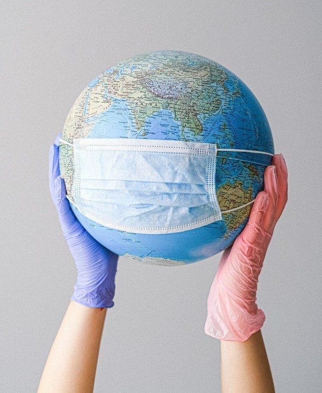 two gloved hands holding up a globe with a mask on it