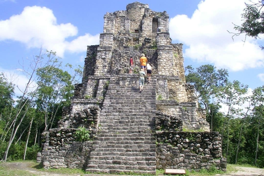 Mayan pyramid with three people walking up