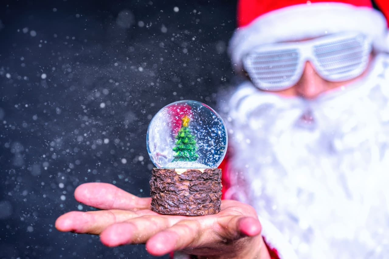 graphic of santa holding snow globe