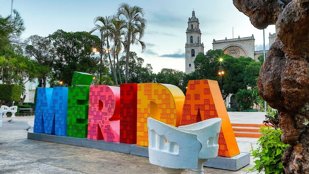 Large multicolor sign spelling Merida in a park plaza