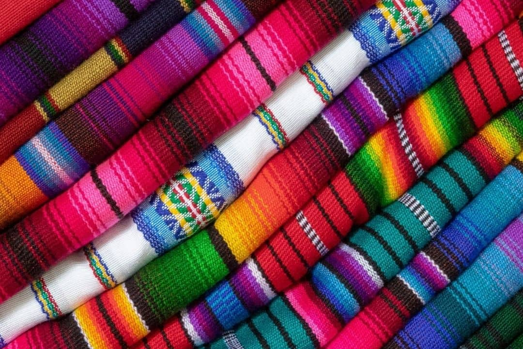 stack of brightly colored folded Mexican blankets