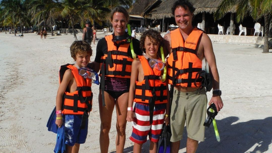 two adults and two children in bathing suits and snorkel gear