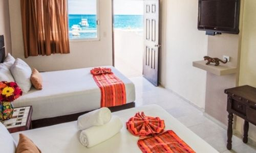 hotel room with two beds and open door with view of the sea