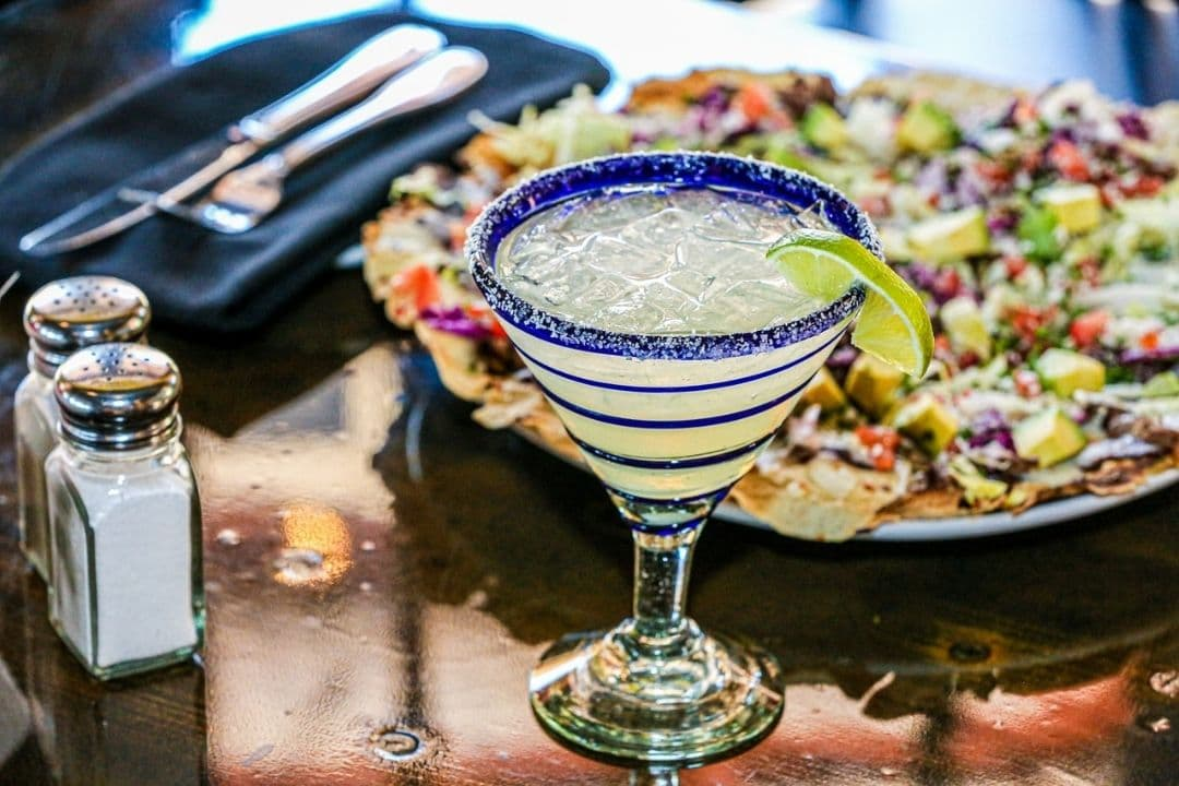 Margarita drink in blue swirl glass with lime wedge and food plate in background