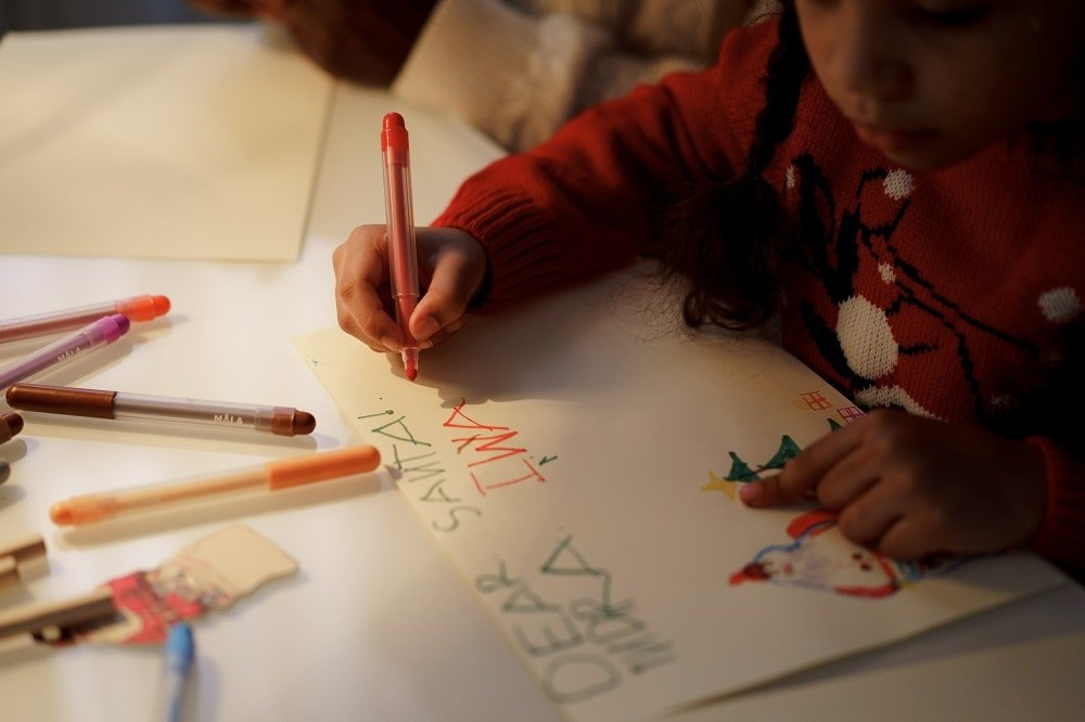 little girl writing a dear santa letter