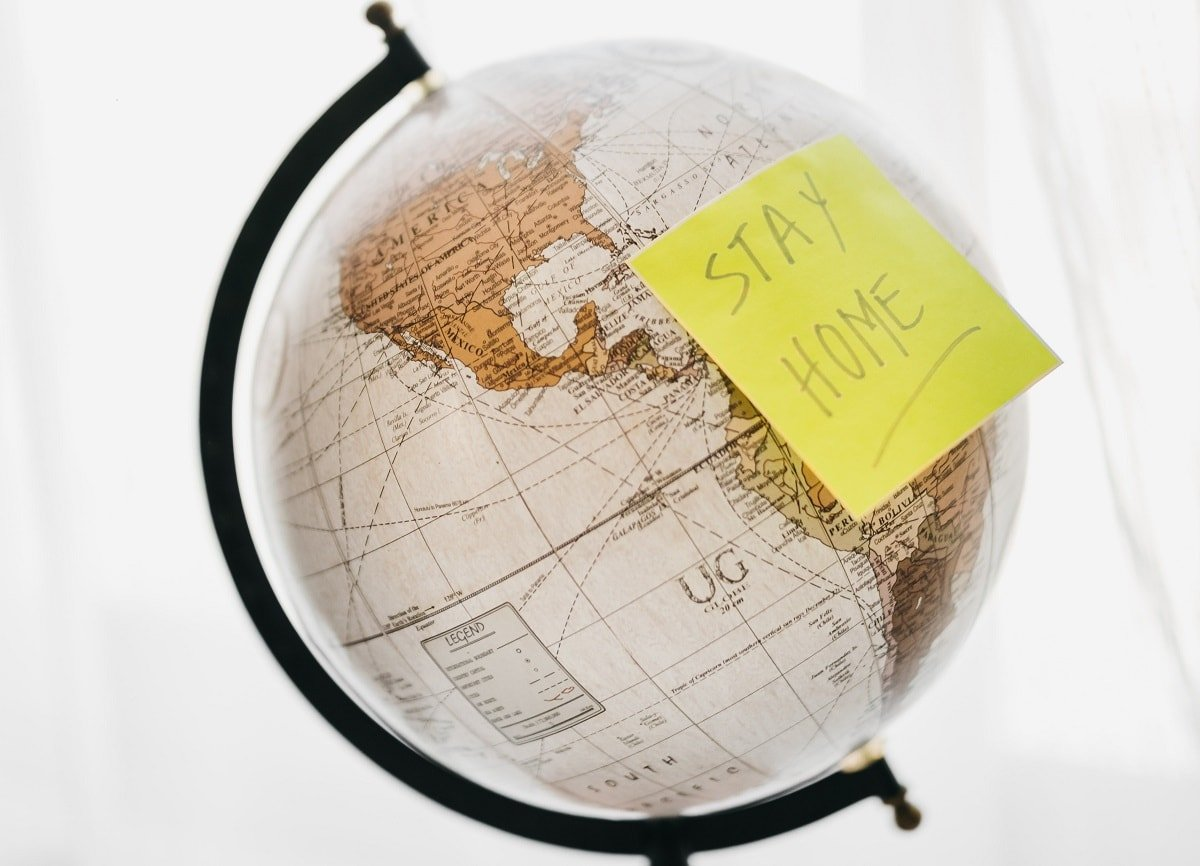 globe with yellow post-it saying stay home
