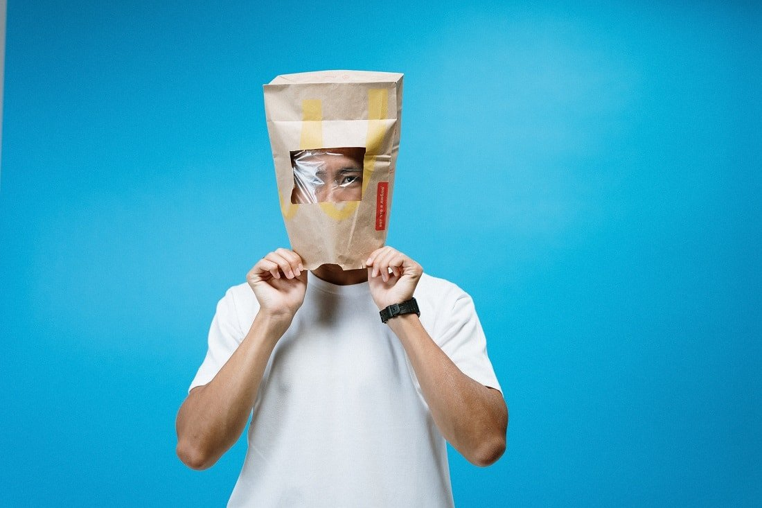 man in white t-shirt with paper bag over his head