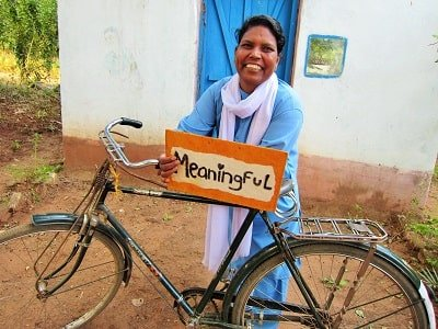 woman standing with bike holding sign saying meaningful