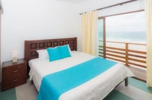 bed with white sheets and light blue sash and matching pillows with open window facing the sea