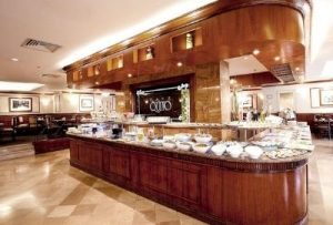 large triangle-shaped hotel breakfast buffet loaded with plates and food