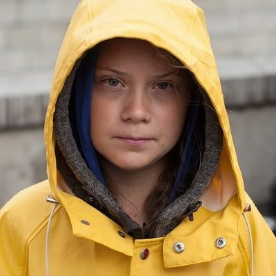 Girl with serious face dressed in yellow hooded raincoat