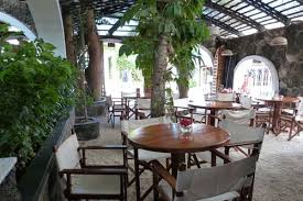 dining area in open courtyard with tree and round tables and chairs