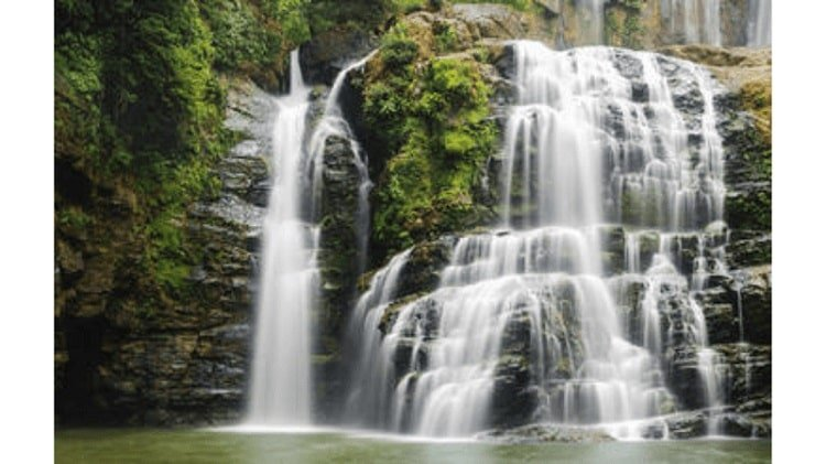 waterfall cascading over large rocks in a green jungle setting