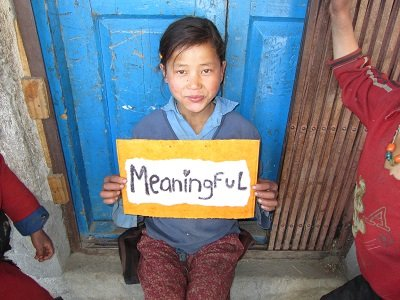 young girl holding sign saying meaningful
