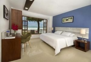 large hotel room with brown furniture, large white bed, and open window facing tree and beach