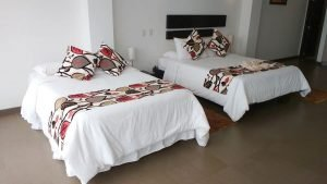 two beds with white bedspreads and sashes and matching pillows with large lead design