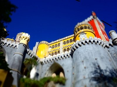 yellow and stone medieval castle with deep blue sky