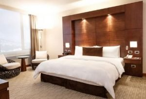 large bed with white bed cover and large ceiling-height brown backboard